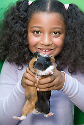 Young girl holding up a guinea pig,