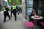 London, UK. Tuesday 11th June 2013. Woman texting on her phone outside a cafe as police turn the corner marching after protesters during demonstration against the upcoming G8 summit in central London, UK.
