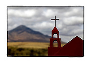 SHOT 2/1/10 1:31:40 PM - A small steel capilla along Highway 2 near Naco, Mexico. Roadside capillas, or tiny chapels, in the Mexican states of Nayarit, Sinaloa and Sonora. The capillas are common along the roads and highways of Mexico which is heavily Catholic and are often dedicated to certain patron saints or to the memory of a loved one that has passed away. Often times they contain prayer candles, pictures, personal artifacts or notes. (Photo by Marc Piscotty / © 2010)