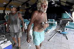 """Cudjoe Key resident Bob Skinner, 84, walks away with some cold water from Mark Lum, 57, who rode out powerful Hurricane Irma with his dog, Cruzan, and another friend in the Venture Out Condominium's bathhouse. """"We felt like the world was coming to an end,"""" said Lum on Tuesday, September 12, 2017. Venture Out is a community of stilt houses, mobile homes and RVs many of which were destroyed by Hurricane Irma. in Cudjoe Key, FL, USA Photo by Taimy Alvarez/Sun Sentinel/TNS/ABACAPRESS.COM"""