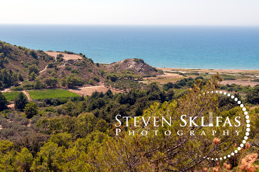 Rhodes. Greece. View from the acropolis of Ancient Kameiros of the coastline and surrounding fertile landscape that's dotted with olive groves and pinewoods.