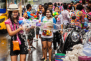 14 APRIL 2013 - BANGKOK, THAILAND:  A woman reacts to get hitting by water in a water fight on April 14, 2013 in Bangkok, Thailand. The Songkran festival is celebrated in Thailand as the traditional New Year's Day from 13 to 15 April. The throwing of water originated as a way to pay respect to people and is meant as a symbol of washing all of the bad away. PHOTO BY JACK KURTZ