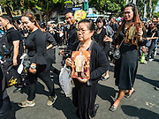 22 OCTOBER 2016 - BANGKOK, THAILAND: Mourners carrying portraits of the late Bhumibol Adulyadej, the King of Thailand, walk into the Grand Palace Saturday. Sanam Luang, the Royal Ceremonial Ground, was packed Saturday with more than 100,000 people mourning the Monarch's death. The King died Oct. 13, 2016. He was 88. His death came after a period of failing health. Bhumibol Adulyadej was born in Cambridge, MA, on 5 December 1927. He was the ninth monarch of Thailand from the Chakri Dynasty and is also known as Rama IX. He became King on June 9, 1946 and served as King of Thailand for 70 years, 126 days. He was, at the time of his death, the world's longest-serving head of state and the longest-reigning monarch in Thai history.       PHOTO BY JACK KURTZ