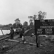 """GI's crossing a temporary bridge over the Danube River in Austria. Sign says, """"The Danube, Just Another Damn River."""""""