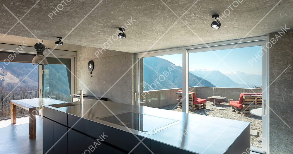 Modern white kitchen with large island, induction hob, sink and stainless steel top. Large windows overlooking the nature of Switzerland. Nobody inside