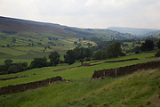 View Swaledale from Reeth across fellside fields of farmland and dry stone walls. Yorkshire, England, UK. This is a farming area where rural living and the countryside is at the centre of life in this county. Swaledale runs broadly from west to east. To the south and east of the ridge a number of smaller dales. Swaledale is a typical limestone Yorkshire dale, with its narrow valley-bottom road, green meadows and fellside fields, white sheep and dry stone walls on the glacier-formed valley sides.