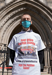 © Licensed to London News Pictures. 23/04/2021. London, UK. A man wears a t-shirt in support of Post Office sub-postmasters outside The High Court. The Appeal Court is ruling on the convictions of a group of 42 sub-postmasters - some of whom were jailed for stealing money after the Horizon accounting software was installed at Post Offices. At a previous High Court hearing a judge found the Fujitsu accounting system had major faults and defects. The Post Office has already agreed to pay £58m in a settlement with more than 500 sub-postmasters<br /> Six convictions were overturned last year . Photo credit: Peter Macdiarmid/LNP