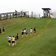Participants run up the hill to take part in a Zorb ride. The sport of Zorb globe riding was invented in New Zealand and globes are designed, manufactured and tested there, The Zorb globe is an 11 foot high inflatable transparent sphere which you can ride inside. Two feet of air protect you from the ground enabling you to globe ride down hills at high.  Agrodome, Western Rd. Ngongotahaha.  Rotorua, New Zealand,, 11th December 2010 Photo Tim Clayton.