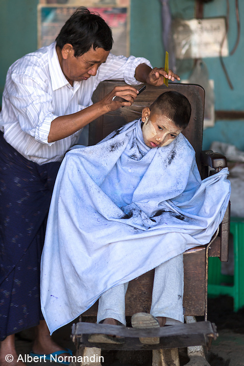 Boy at barber shop resisting a haircut, Nawnghkio, Hsipaw