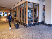"""20 MARCH 2020 - DES MOINES, IOWA: A person walks through the lobby of 801 Grand, the tallest office tower in Iowa, Friday morning. The building is a part of the campus of Principal, a large financial services company. The building was shutdown Friday after a visitor tested positive for COVID-19. Some workers were placed in self quarantine and all were ordered to work from home. On Friday morning, 20 March, Iowa reported 45 confirmed cases of the Coronavirus. Restaurants, bars, movie theaters, places that draw crowds are closed for at least 30 days. There are no """"shelter in place"""" orders in effect anywhere in Iowa but people are being encouraged to practice """"social distancing"""" and many businesses are requiring or encouraging employees to telecommute.      PHOTO BY JACK KURTZ"""