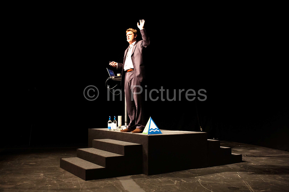 A motivational guru is standing on a podium to address an audience of Ernst & Young staff during their annual Academy Day held for 3,000 of company London employees at Excel in London's Docklands, England. Standing confidently on his rostrum with a laptop computer, bottled water and a pyramid as teaching aids, he holds his hand to encourage the personnel to participate by offering their ideas and input dring the seminar. Each employee attending this fair where motivational pep-talks from executives, outside speakers and gurus will talk to large groups of E & Y personnel so their presence on this day away from the office is vital for the year's business ahead.
