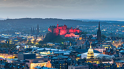 Evening view of Edinburgh Castle illuminated in red and skyline of city from Salisbury Crags, Edinburgh, Scotland, United Kingdom.
