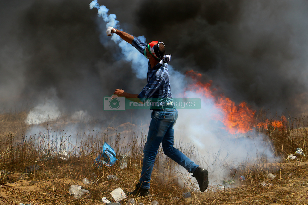 """April 27, 2018 - Clashes break out between Palestinian demonstrators and Israeli soldiers east of the Gaza city of Khan Yunis, along the Gaza- Israeli border, on the fifth consecutive Friday of the 'Great March of Return' protest. Palestinian demonstrators threw stones at the Israeli forces, while Israel soldiers fired back tear gas, sponge-tipped bullets, and live ammunition, injuring a number of protesters. Palestinians also burned tires to create black smoke and hide from the fire of a high number of Israeli snipers deployed at the Israeli side of the border. Hamas's leader Yahya Sinwar joined the protest. Palestinian have been holding the """"Great March of Return"""" protests to demand the right of the Palestinian refugees to go back to their ancestral lands in what is now Israel, and their right to a dignified life in Gaza through the lifting of the Israeli blockade on the Palestinian enclave (Credit Image: © Ahmad Hasaballah/IMAGESLIVE via ZUMA Wire)"""