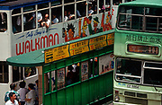 While still a British colony, 1990s tram passenger commuters stop at a tram and bus stop on the des Voeux road in the direction of Wanchai and Causeway Bay, on 21st April 1995, in Central, Hong Kong, China.