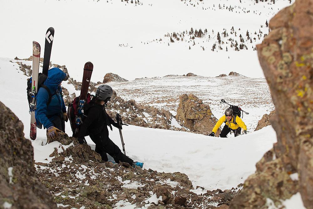 Backcountry skier Judd MacRae gains the summit ridge of Hayden Peak and his waiting friends, San Juan Mountains, Colorado.
