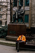 A trader from the LIFFE futures exchange takes a break in the street during a weekday lunchtime, beneath the statue of George Peabody in the City of London. Wearing the orange jacket of this once thriving financial instutution, we see a scene of wealth and prosperity, from an era of growth during the industrial revolution to the arrogance and self-indulgence during the government of John Major - a political inheritance from Margaret Thatcher. Peabody was a philathropist, banker and entrepreneur ( 1795 – 1869).
