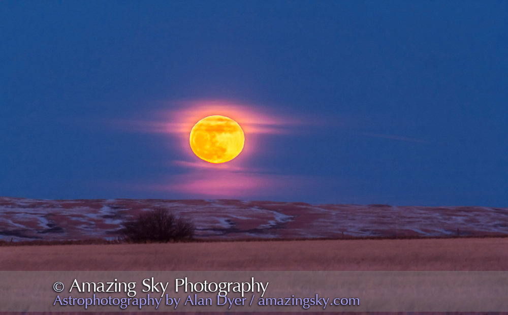 """The rising of the Full """"Snow"""" Moon of February 2016, on Feb 22, over the fields to the east of my house in southern Alberta. This is a single exposure with the Canon 60Da and 200mm lens with 1.4x extender, taken at the end of an HD video sequence. Exposure was 1/15 second at f/5.6 at ISO 200."""