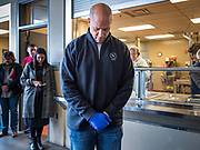 27 NOVEMBER 2019 - DES MOINES, IOWA: US Senator CORY BOOKER (D-NJ) bows his head in prayer before lunch at Central Iowa Shelter and Services in Des Moines. Sen Booker helped plate up and serve lunch at the shelter. The shelter has about 180 beds and is full almost every night. In January and February, more than 250 people per night come to the shelter, which sets out overflow bedding. Senator Booker is running to be the Democratic nominee for the US Presidency in 2020. Iowa hosts the first selection event of the presidential election season. The Iowa caucuses are February 3, 2020.         PHOTO BY JACK KURTZ