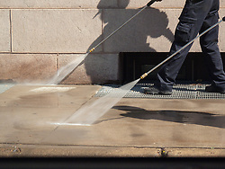 Work personnel clean the sidewalks of Minneapolis using power washers