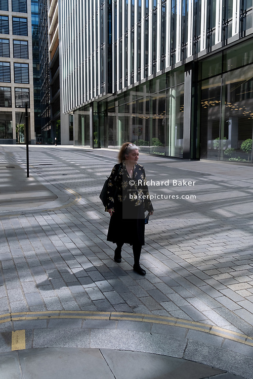 A lady walks down a street with reflected light from plate glass windows in the City of London, the capital's financial district which is still largely quiet as workers continue to work from home during the on-going Coronavirus pandemic,  on 6th August 2020, in London, England.