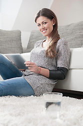 Portrait of smiling young woman with digital tablet sitting on carpet at home