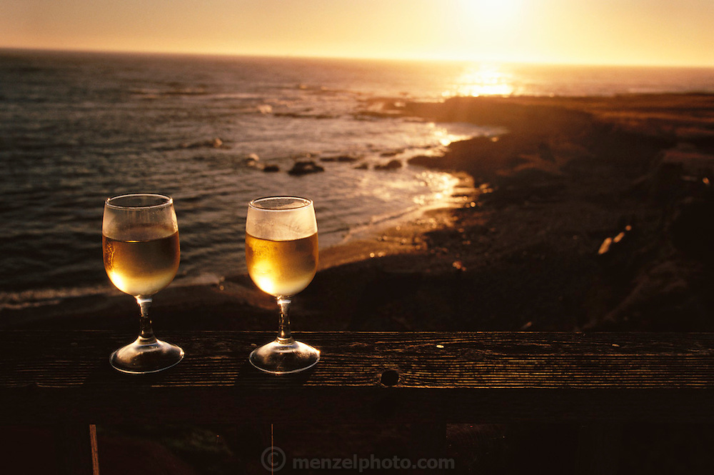 Northern California Coast: Shelter Cove (Lost Coast) in Humboldt County. Two glasses of cold white wine on the rail of the Lighthouse Inn at sunset with the Pacific Ocean in background.