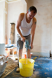 Man using mixing tool to stir plaster in a bucket,