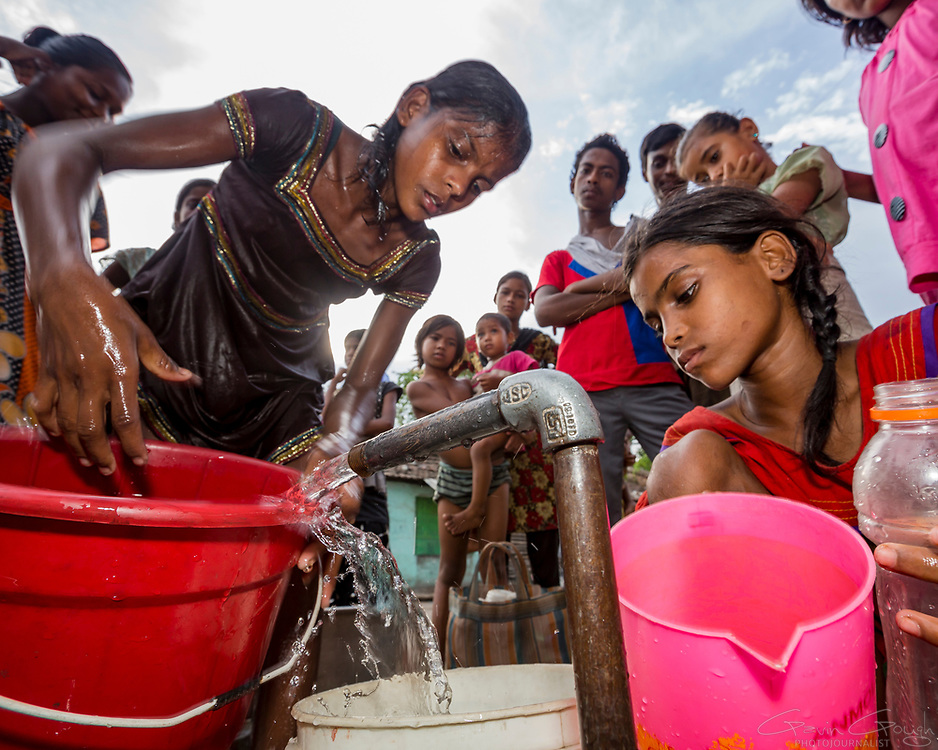 Meera, a young woman living in the slum, fills buckets with water from a standpipe, Tangra slum, Dhipi, Kolkata, India