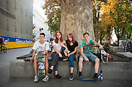 Ukrainian teenagers, holding a skateboard, scooter, and smartphone, enjoy a late summer afternoon outdoors in Odessa, Ukraine<br /> <br /> (September 2016)