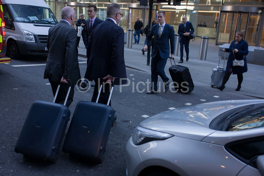 Businessmen and others tow baggage as they cross Fenchurch Street in the City of London. Pulling their identical suitcases across the busy road, the two associates have the same items behind them. In front, we also see others coming the other way, each with hands on handles as they wheel their possessions behind them in the heart of the capital's financial district aka The Square Mile.