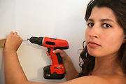 Woman in her 30s hangs up shelves with a power tool Model Release available