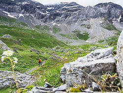 Woman hiking in the High Pyrenees on small path through Cirque de Troumouse, France