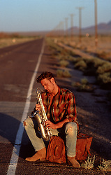 man on the side of an empty road playing the saxophone