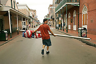 Elton Driscoll, Jr. carries a U.S. flag that he removed from a hotel down the deserted and boarded-up Bourbon Street in the French Quarter of New Orleans August 28, 2005. Authorities in New Orleans ordered hundreds of thousands of residents to flee on Sunday as Hurricane Katrina strengthened into a rare top-ranked storm and barreled towards the vulnerable U.S. Gulf Coast city. REUTERS/Rick Wilking