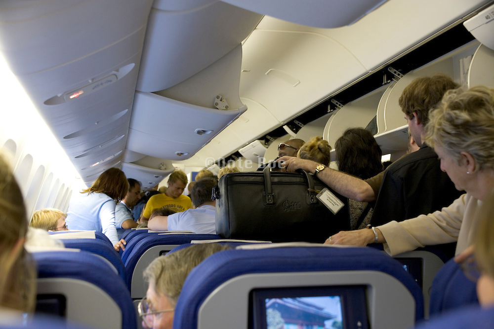 waiting in the aisle to leave the airplane