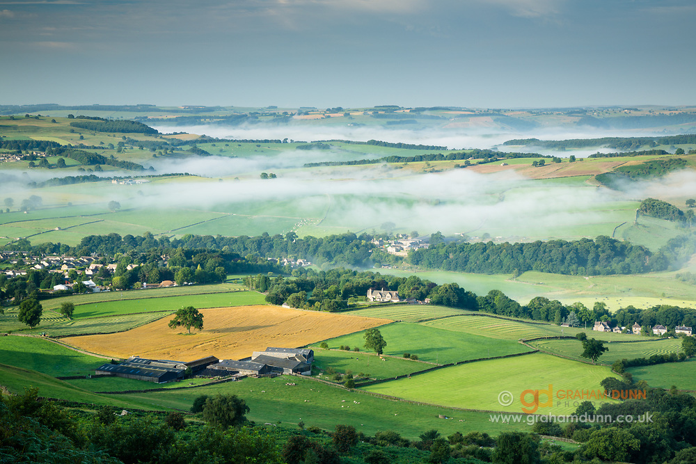 Baslow village surrounded by fields in the Derwent Valley and the White Peak's undulating limestone plateau partially enshrouded in mist in the distance. Captured from Baslow Edge. Derbyshire, Peak District National Park, England, UK. Summer, August.