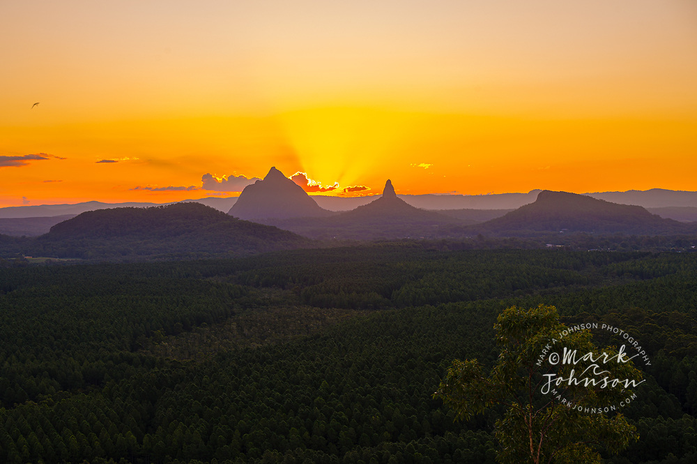 The setting sun behind Mt Beerwah & Mt Coonowrin, Glass House Mountains, Sunshine Coast, Queensland, Australia