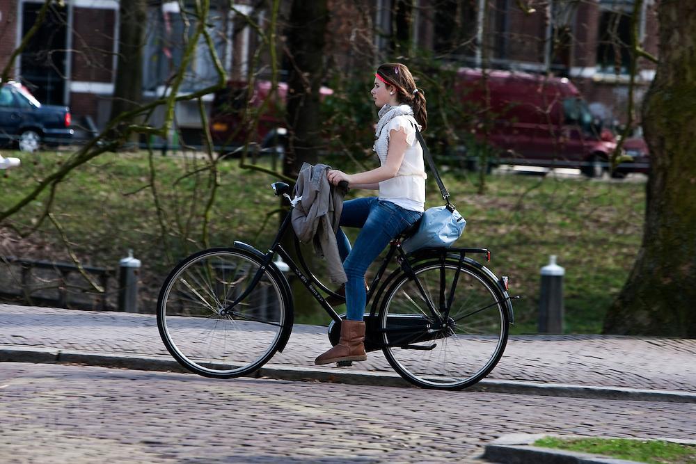 Een meisje fietst op een omafiets door Utrecht