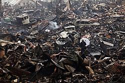 A man makes his way through devastated Shishiori township of Kesennuma in Miyagi prefecture, Japan, March 16, 2011.