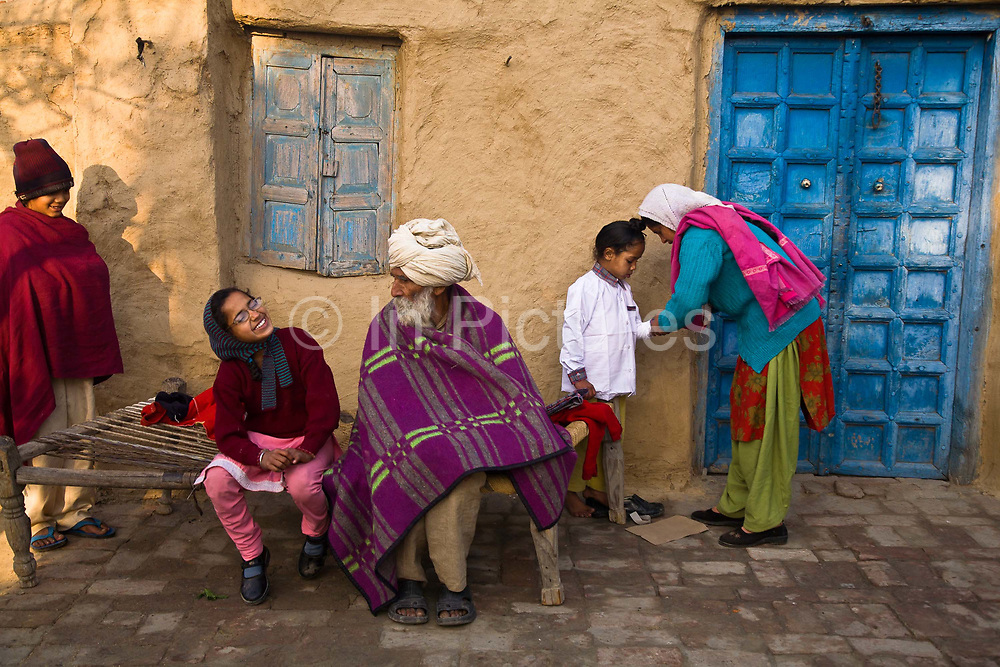 Sikh family dressing for breakfast and shortly after heading for school lessons, Chita Kalaan village, Punjab, India