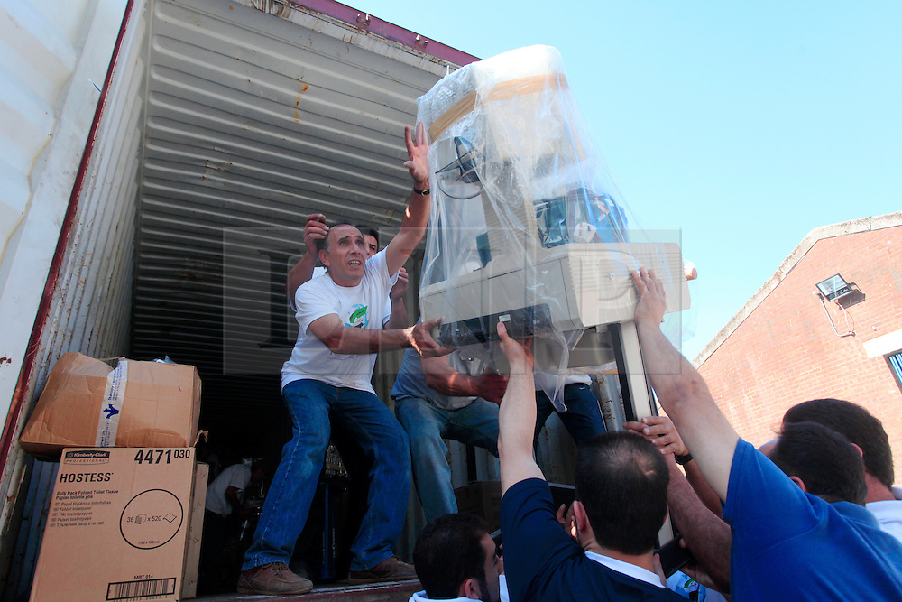 © Licensed to London News Pictures 10/04/2013<br /> Men load medical equipment into a shipping container that has been donated to humanitarian agency Hand In Hand for Syria (HIHS). Equipment will then be delivered to some of the 56 field hospitals inside Syria that HIHS supplies.