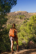 A hiker stops to look at the Hollywood sign from the Mt. Hollywood Trail in Griffith Park, Los Angeles, California.  (model released)