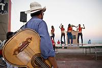 Street musician watching female dancers during celebrations around San Felipe Baja 250 off road race, San Felipe, Mexico