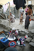 Farida, 33, at left, the second wife of Noor Agha, washes clothes as Marzia, 46, at right, the first wife, stands with their children, in their house (girls on the left are their relatives), Kabul, Afghanistan, Friday, Aug. 10, 2007. Noor Agha is a renowned kite maker who made kites for the movie makers of the best-selling novel, The Kite Runner, which will be distributed by Dreamworks and Paramount Vantage in Nov. this year. Noor Agha's wives, using their special glue, help him produce enough kites to please the clients' needs. Some of his children can also make their own kites with plastic bags and bamboo sticks. As the Afghan New Year's Day (Nawruz) approaching on March 21, the finger tips of Noor Agha's family got busier for mass production.