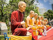 20 APRIL 2015 - BANGKOK, THAILAND:   A woman looks at large statues of revered Buddhist monks set up for Songkran, the tradition Thai New Year, in Benchasiri Park along Sukhumvit Road in Bangkok.   PHOTO BY JACK KURTZ