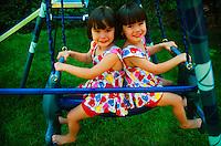 Four year old twin girls on swings, Danbury, Connecticut USA
