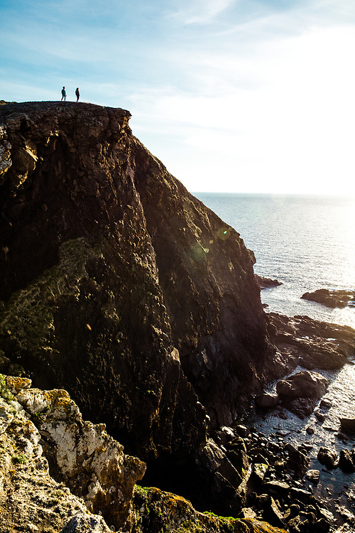 Silhouettes of a couple walking at the edge and top of a cliff on the coast of Jersey, Channel Islands, near Plemont at sunset