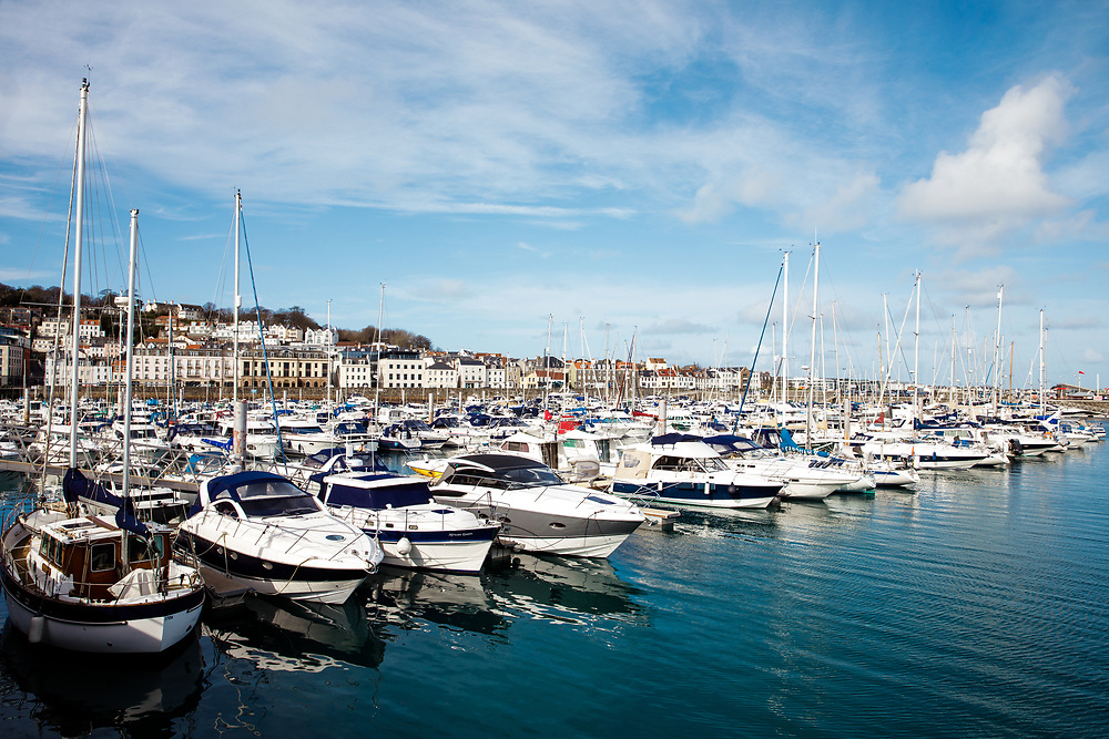 Houses and apartments overlooking the yachts and speed boats moored up in St Peter Port marina in the Channel Islands