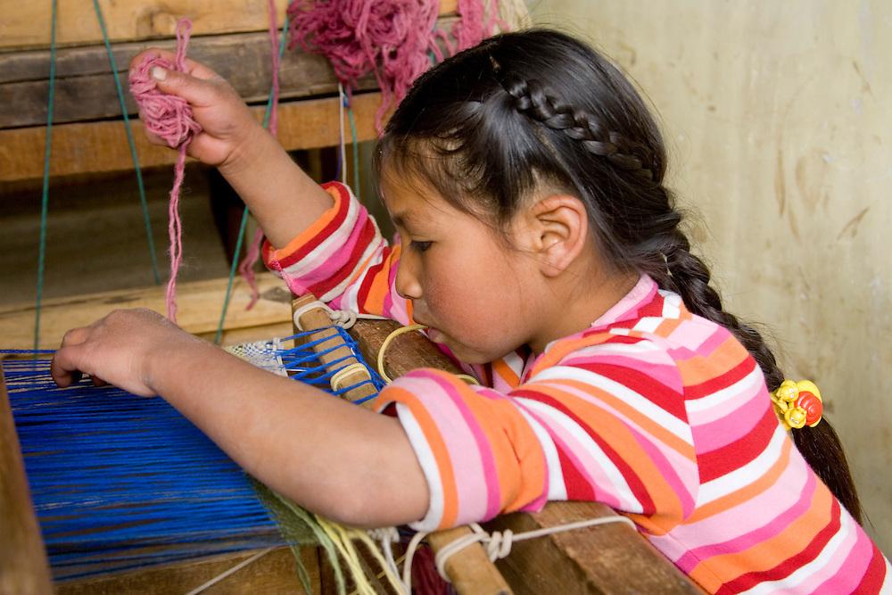 Girl (age 9) weaving at loom, Huaripampa (near Huaraz), Peru, South America  MR