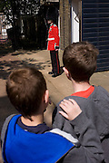 24 hours before the royal marriage of Prince William and Kate Middleton, a guardsman stands by his sentry box in front of Clarence House in St James Palace where the royal bride is staying. Two young brothers stand admiring the soldier in his bright red uniform. Taking place on Friday 30th April in front of millions of Britons and foreign tourists (many American), the crowds are already gathering to claim their ideal locations in the front rows along the procession route.
